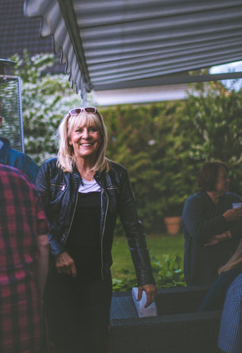 Smiling woman with friends in yard