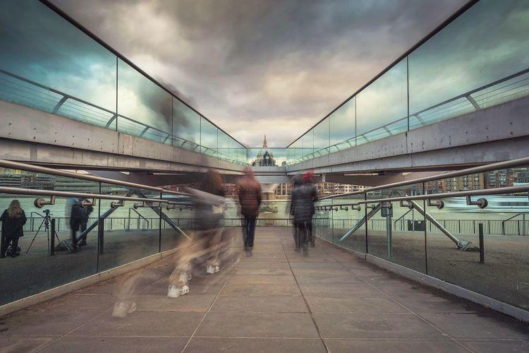 Blurred motion of people on london millennium footbridge in city