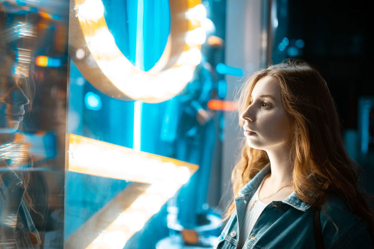 Portrait of young woman looking at illuminated mirror