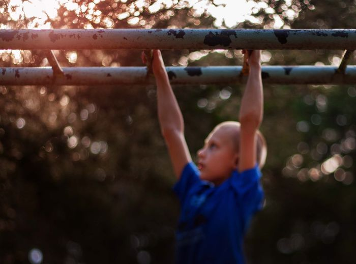 Side view of boy hanging on monkey bars at playground during sunset