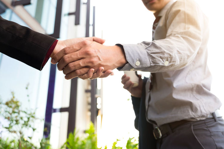 Midsection Of Businessman Holding Hand With Colleague