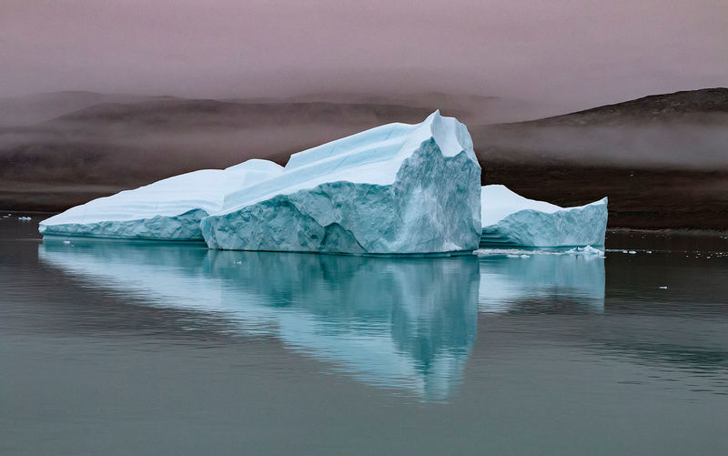 The blues of the icebergs in Greenland Icebergs Iceberg Greenland Reflection Water Reflections Blue Ice Floe Clouds Dark Sky