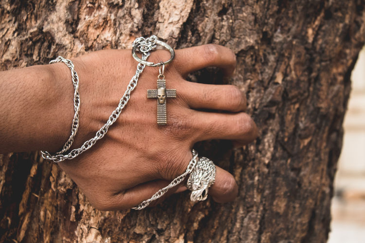 Cropped hand holding crucifix on tree trunk