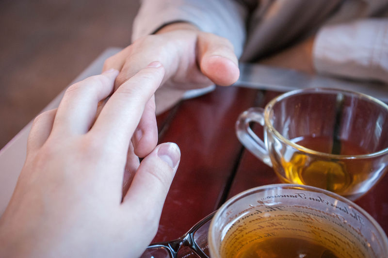 Close-up of couple holding hands on table with tea cups
