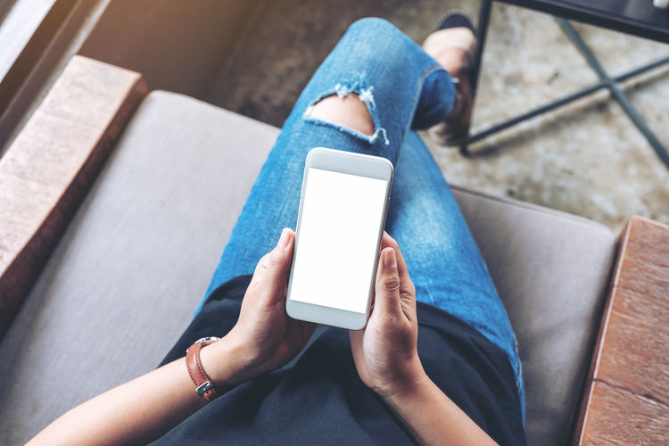 Low section of woman using mobile phone while sitting at home