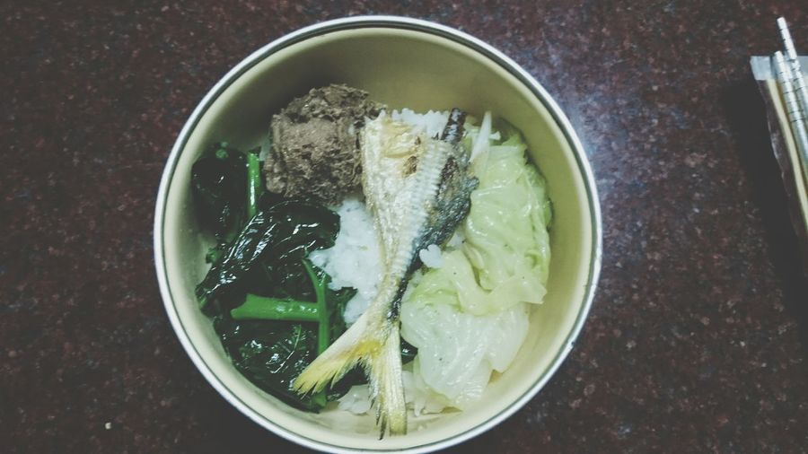 High Angle View Of Fish Rice Prepared With Green Leafy Vegetable On Frying Pan