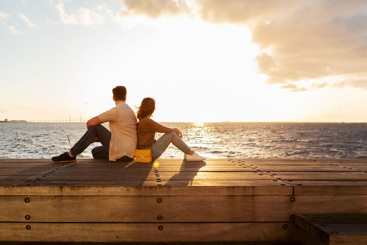 Men sitting on wood by sea against sky during sunset