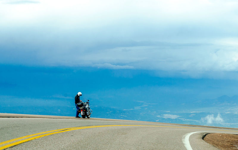 Person standing with motorcycle at roadside