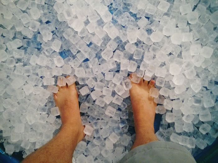 Low Section Of Man Standing On Ice Cubes