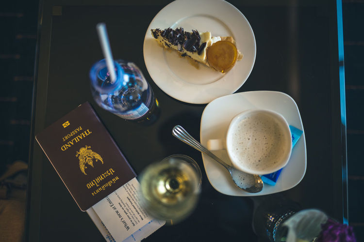 Directly above shot of passport with drinks and dessert on table