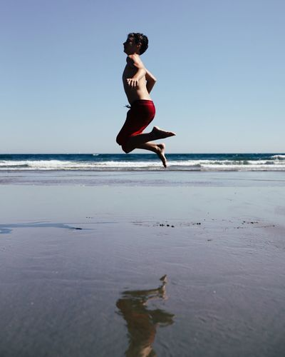 Full length of young man jumping on beach against clear sky
