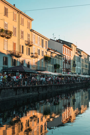 After Work Drinking Coffee Water Reflections Architecture Building Exterior Built Structure City Clear Sky Day Evening Italy Large Group Of People Leisure Activity Men Nature Outdoors People Real People Reflection Sky Spotify Water Waterfront