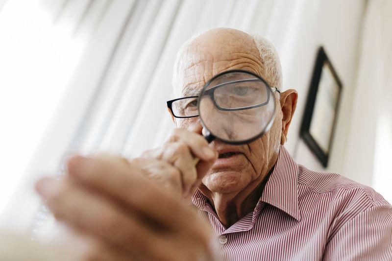 Portrait of man holding eyeglasses
