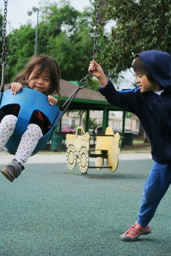 Boy pushing sister riding on swing in park