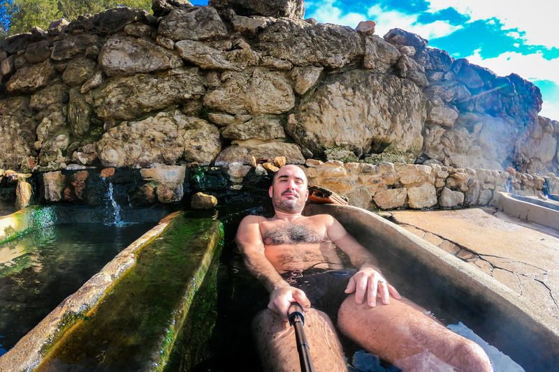 Bande SPAIN Aquis Querquennis Spa Roman Spa Thermal Pool Thermal Bath Thermal Waters Natural Thermal Pools Roman Thermal Spa Roman Bath Enjoying Outdoor Pools Outdoors Vacations Travel Galicia Ruins Water Rock Man Selfie Relaxing Stone Bathtub