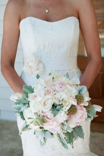 Midsection of bride holding flower bouquet