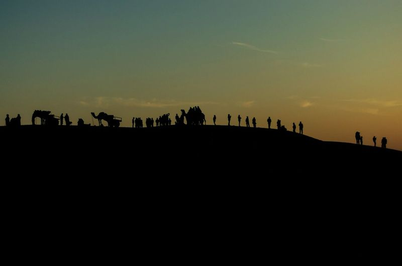 Silhouette people on landscape against clear sky