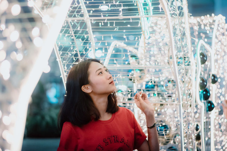 Merry Christmas. Christmas Christmas Lights Christmas Decoration Christmas Ornament Christmas Themes One Person Leisure Activity Lifestyles Real People Headshot Looking Indoors  Casual Clothing Portrait Hair Women Front View Focus On Foreground Long Hair Black Hair Transparent Child Glass - Material Hairstyle
