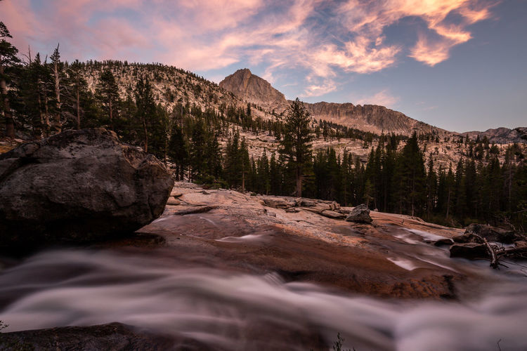 Suffused with pink | JMT DAY 8 - TULLY HOLE AT SUNSET Tully Hole at sunset When we arrived at Tully Hole, where the JMT meets the trail to McGee Pass, the light sprinkling, which had already begun since we left Lake Virginia, turned into a shower. Thankfully though the dense forest sheltered us a little bit while setting up our camp. Once the rain stopped, hikers holed up inside their tents the whole time since we got there started crawling out. By then we were already done with our dinner and started scouting the area. My hope was to cross Fish Creek, running parallel to the creek till it diverged into Cascade Valley, and to find a higher vantage point where I could frame the area with the sun in the background. But no footbridge nor log to cross was in sight. The rapidly flowing water didn't look safe even without camera gear. So, instead of any attempt in vain, I plodded down the trail for about 200 yards till this clearing presented itself. To my eye it was also perfect for night sky. I hopped down the slope toward the creek and set up my cameras fairly close to the water. But, as I waited, the glow that I had expected to see cast on the rocky ridge never materialized. I suspected that the lingering clouds in the west sky must have diffused the light. To my pleasant surprise though, the clouds hovering overhead got suffused with pink. Tully Hole, Sierra National Forest, CA Sky Beauty In Nature Scenics - Nature Mountain Nature Tranquility Tranquil Scene Water Cloud - Sky No People Rock Non-urban Scene Sunset Idyllic Outdoors Flowing Water Flowing Tully Hole, Sierra Nevada Fish Creek, Sierra Nevada Mountains Eastern Sierras Long Exposure Sunset Glow Adventure