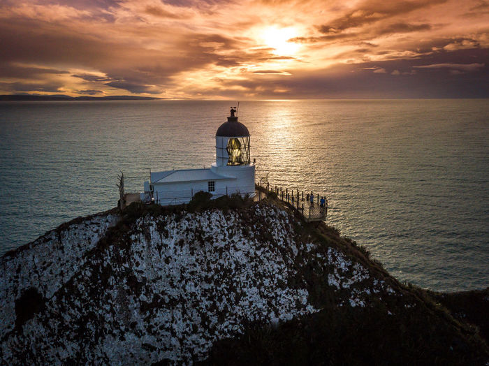 Nugget Point Lighthouse, Dunedin, Otago, New Zealand Dunedin New Zealand Lighthouse Nugget Point Lighthouse Otago Peninsula Beauty In Nature Cloud - Sky Horizon Horizon Over Water Idyllic Mode Of Transportation Nature Nautical Vessel New Zealand Orange Color Outdoors Scenics - Nature Sea Sitting Sky Sunset Tranquil Scene Tranquility Transportation Water The Great Outdoors - 2018 EyeEm Awards
