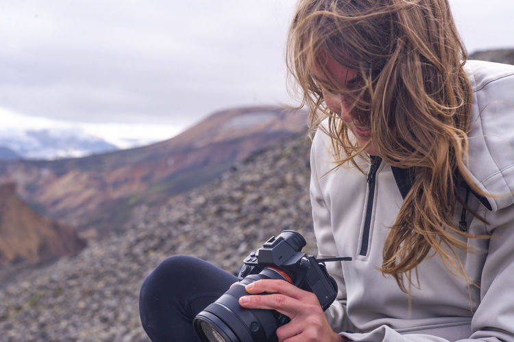Midsection of woman photographing against mountain