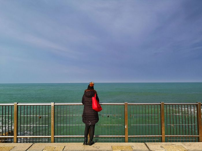 Rear view of woman looking at view of sea while standing by railing against sky