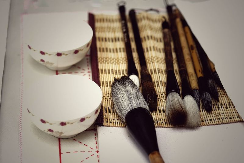 High angle view of bowls and brushes on table