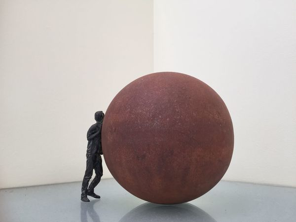 A model of a man rolling a large orb. Design Rust Metal Struggle Moving Forward  Pushing Orb Statue Miniature EyeEm Selects No People Indoors  White Background Close-up Studio Shot Day