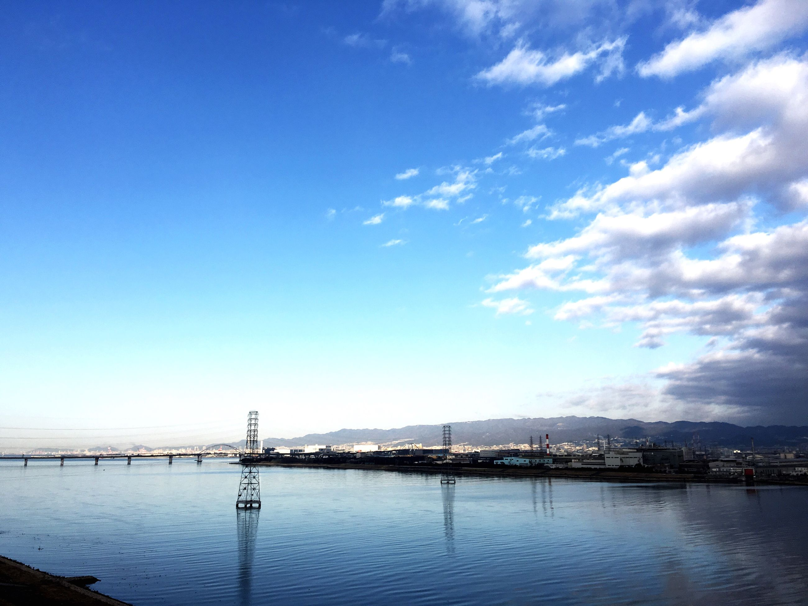 water, sea, sky, waterfront, connection, built structure, blue, architecture, tranquility, tranquil scene, nature, scenics, cloud, river, outdoors, no people, cloud - sky, bridge - man made structure, day, beauty in nature