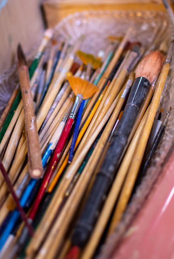 A variety of artist brushes are ready to be used in a pottery work shop