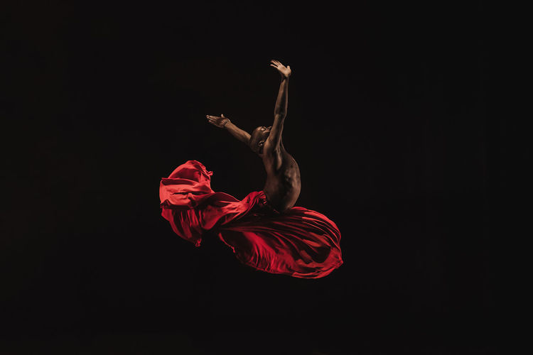 Male ballet dancer performing against black background