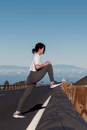 Woman sitting on retaining wall against clear sky