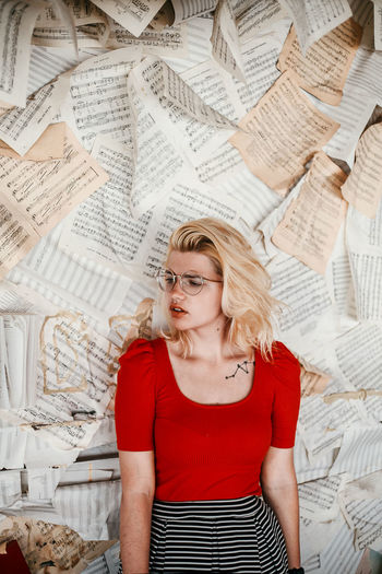 High angel view of young woman standing against papers on wall