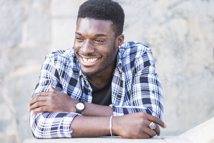 Happy cheerful black african european young man portrait - smile and laugh for happiness and joy - hipster millennial people concept enjoying the lifestyle One Person Young Men Real People Young Adult Smiling Casual Clothing Front View Happiness Day Portrait Lifestyles Beard Sitting Adult Looking Men Checked Pattern Focus On Foreground Emotion Outdoors 20-24 Years City Life Sunlight Afro American Hipster - Person