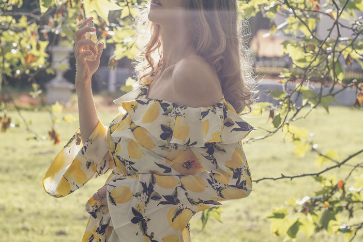 Midsection of woman spraying perfume by tree