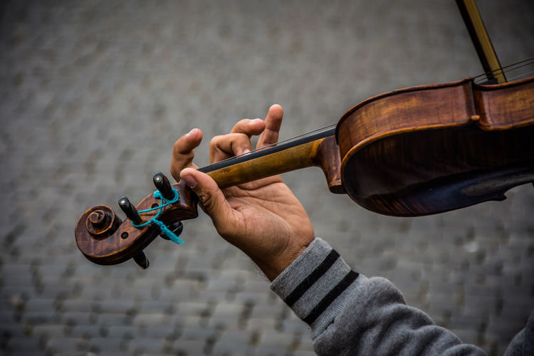 Cropped hand playing violin on footpath
