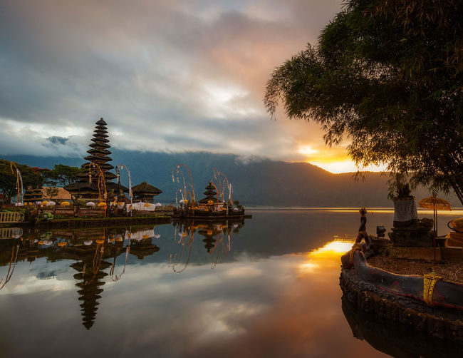 Panoramic view of lake and buildings against sky during sunset