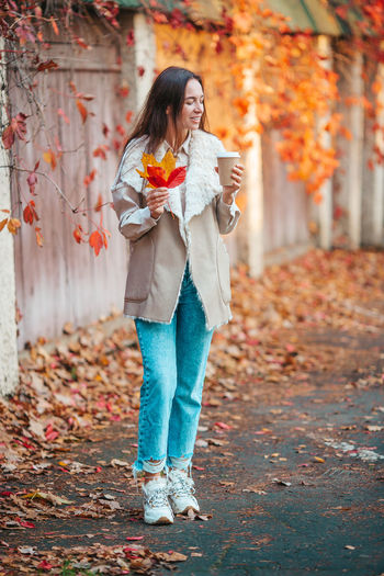 Full length of woman standing by autumn leaves