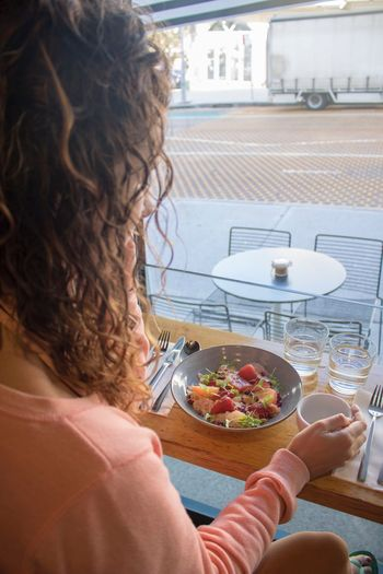 Close-up of woman eating breakfast while sitting at table in restaurant
