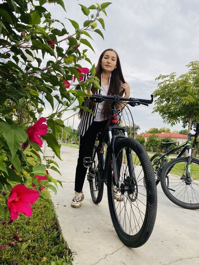 Woman standing on bicycle by flowering plants