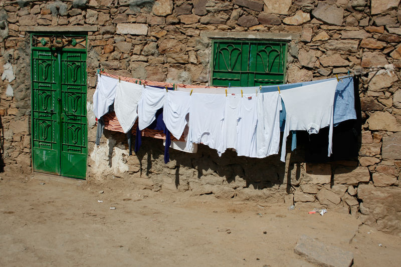 White laundry hanging out to dry outside a stone walled house with green doors Building Exterior Green Color White Color Textile House Hanging Wall No People Laundry Drying Clothing Clothesline Window Stone Wall Wall - Building Feature Built Structure Architecture Building Outdoors Day