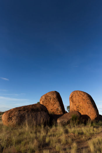 Sunset at the Devils Marbles, Australia. Incredible atmosphere between those unreal rock formations. They look as if they are burning in the sunlight. Beauty In Nature Blue Clear Sky Day Devils Marbles Grass Karlu Karlu Landscape Nature No People Orange Outback Outdoors Rock - Object Rock Formation Scenics Sky Stones
