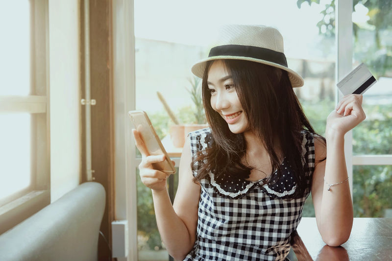 Young woman holding credit card and using smartphone Banking Beautiful Business Buying Consumer Credit Card Customer  Discount Fashion Happy Internet Lifestyles Mobile Phone Online  Paying People Purchase Shopping Smart Phone Smile Smiling Store Technology Women Young