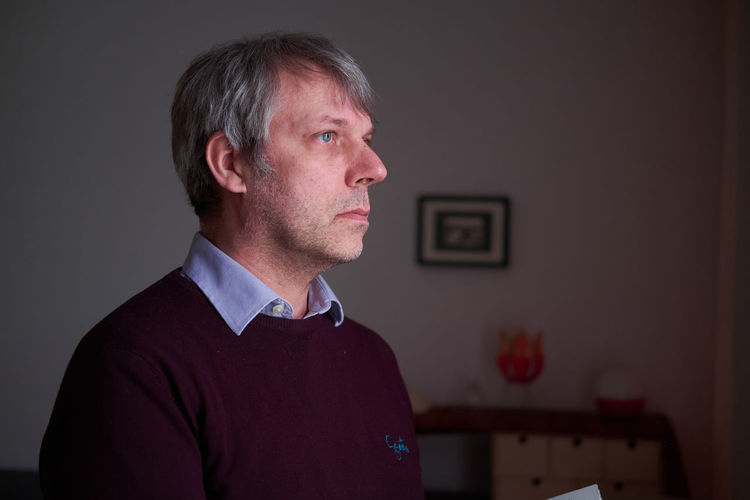 Portrait of man standing against wall at home
