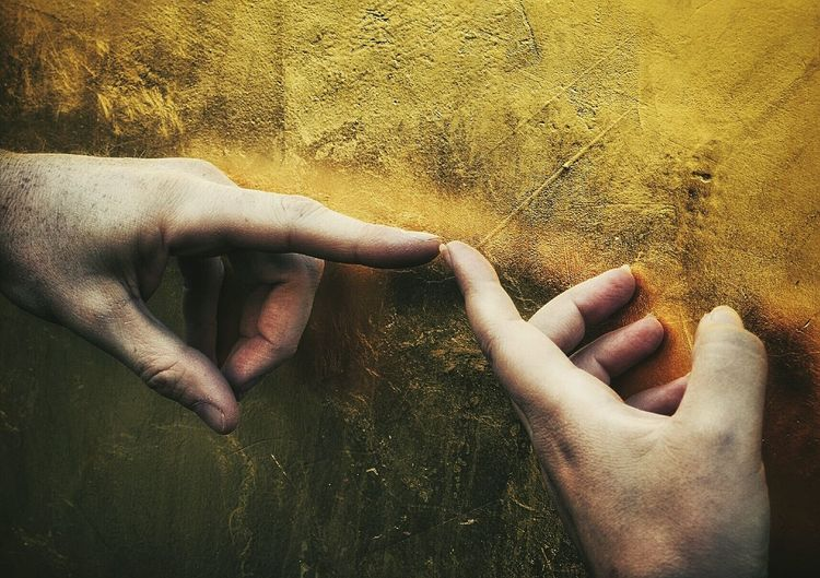 Cropped hands of friends touching by golden wall