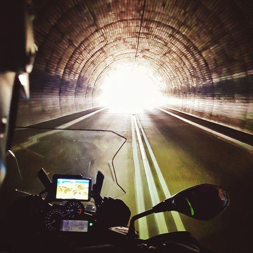 Rear view of man photographing illuminated tunnel