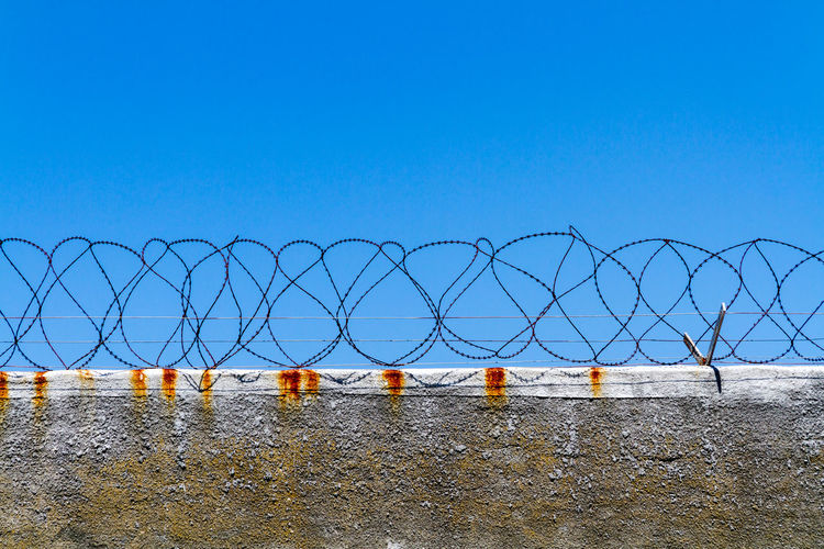 Barbed wire fence against clear sky