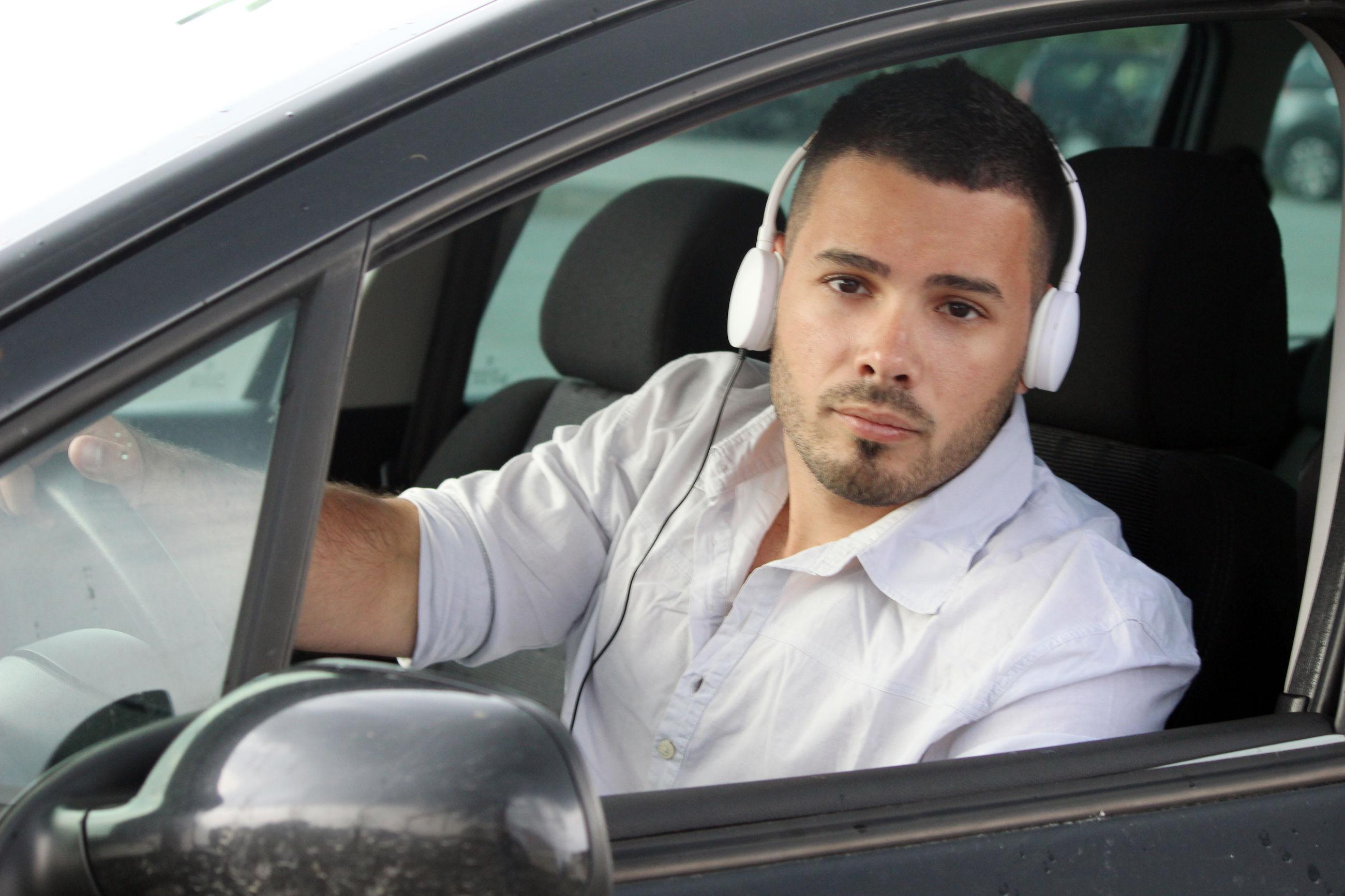 PORTRAIT OF A MAN SITTING ON CAR