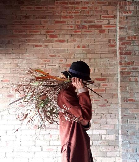 Woman holding umbrella against brick wall