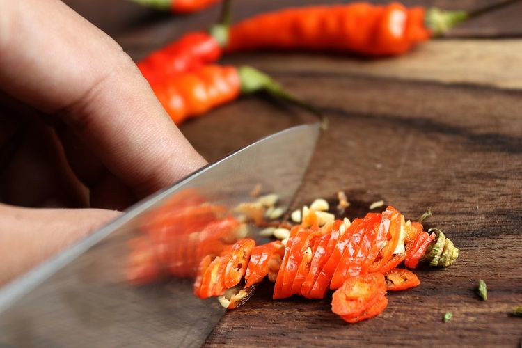 Cropped hand chopping red chili